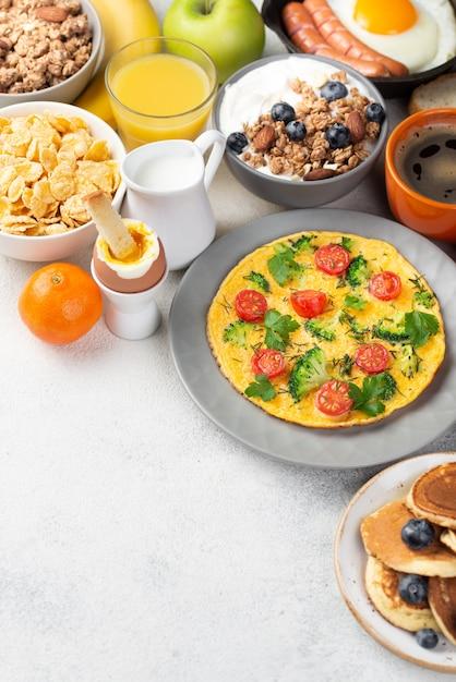 Alto ângulo de omelete com cereais e panquecas no café da manhã Foto gratuita