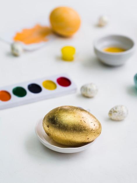 Alto ângulo de ovo de páscoa de ouro com paleta desfocado Foto gratuita