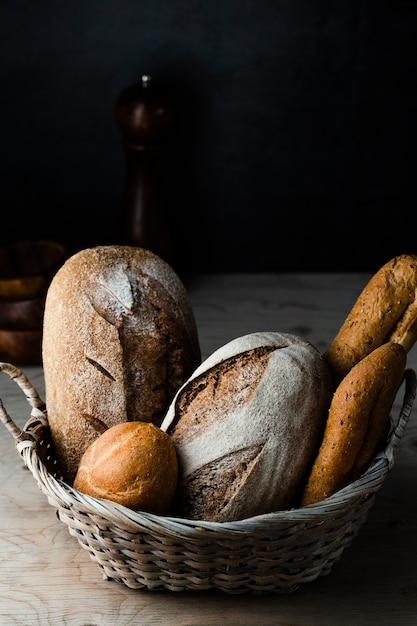 Alto ângulo de pão em uma cesta na mesa de madeira Foto gratuita