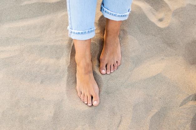 Alto ângulo de pés de mulher na areia na praia Foto gratuita