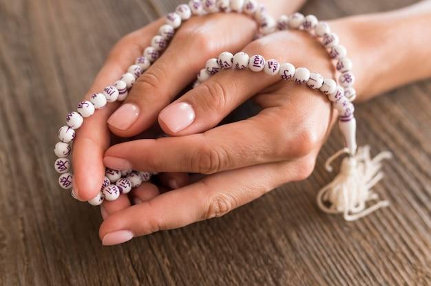 Alto ângulo de pessoa rezando com o rosário nas mãos Foto gratuita