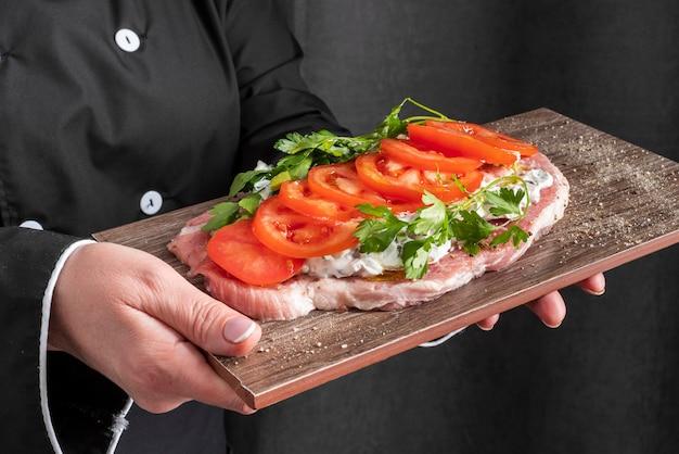 Alto ângulo de prato com tomate realizada pelo chef feminino Foto gratuita