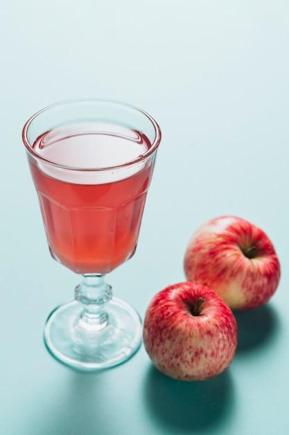 Alto ângulo de suco de maçã no fundo liso Foto gratuita