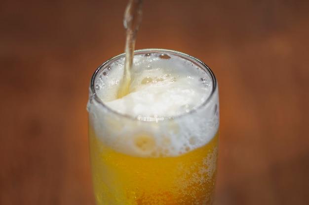 Alto ângulo, derramando cerveja em pinta na mesa Foto gratuita