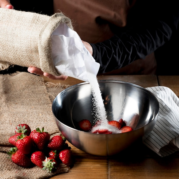 Alto ângulo do chef adicionando açúcar na tigela de morangos Foto gratuita