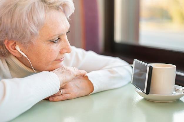 Alto ângulo feminino sênior assistindo vídeos no telefone Foto gratuita