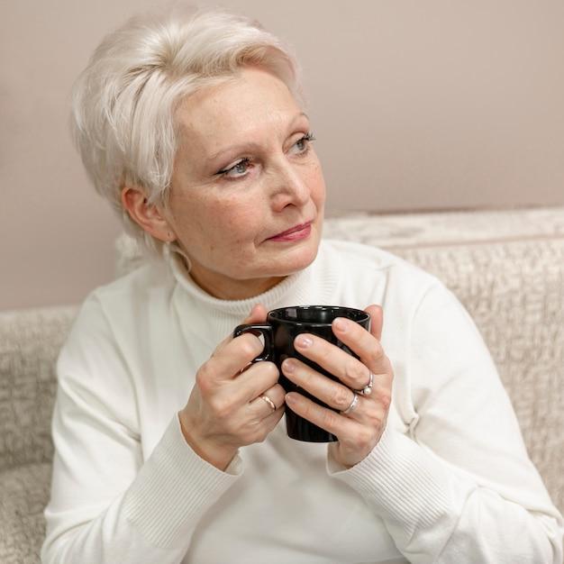 Alto ângulo feminino sênior em casa bebendo café Foto gratuita