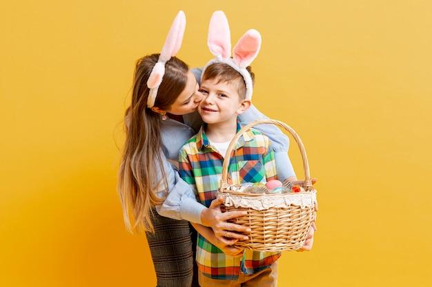 Alto ângulo mãe e filho com cesto de ovos pintados Foto gratuita
