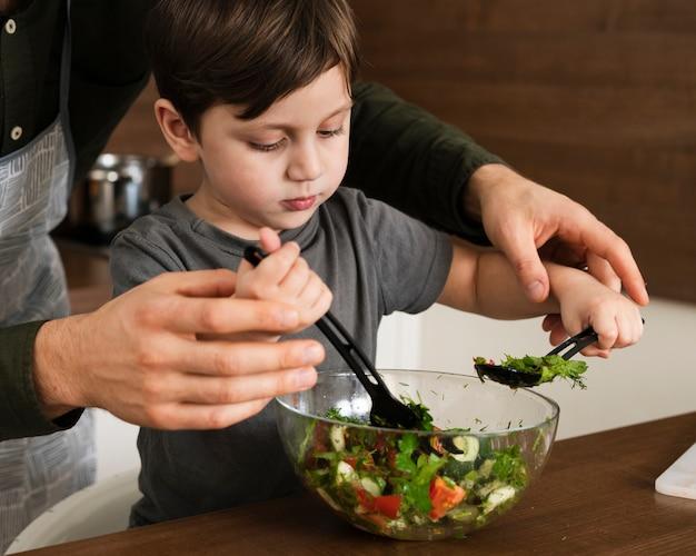 Alto, ângulo, menino, misturando salada Foto gratuita