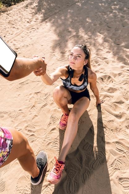 Alto ângulo mulher recebendo ajuda na praia Foto gratuita