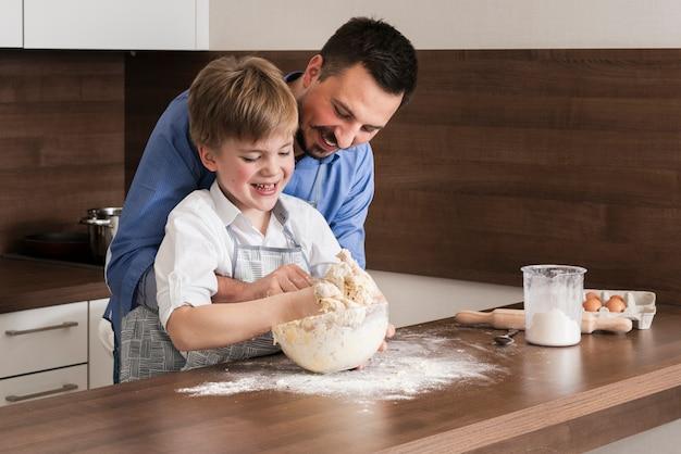 Alto ângulo pai e filho juntos a fazer massa Foto gratuita