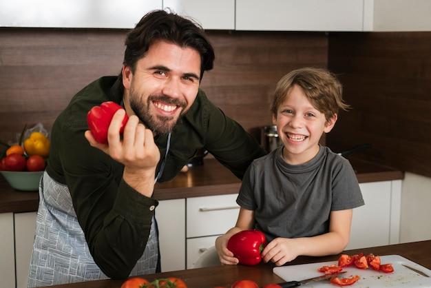 Alto ângulo pai e filho segurando legumes Foto gratuita
