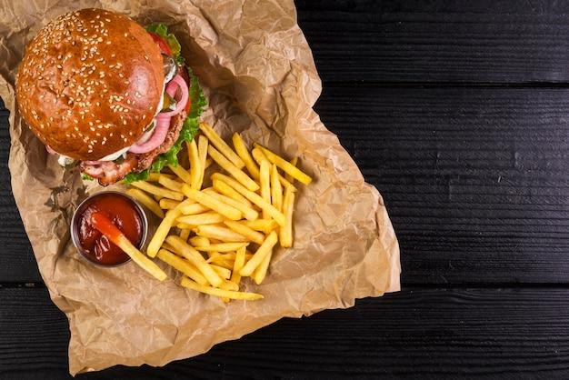 Alto ângulo, tirar hambúrguer de carne com batatas fritas Foto gratuita