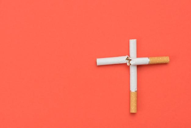 Alto, ângulo, vista, crucifixos, sinal, feito, cigarro, laranja, fundo Foto gratuita