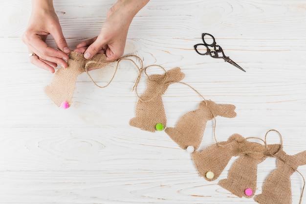 Alto, ângulo, vista, de, mão, cosendo, forma coelho, bunting, ligado, textured madeira Foto gratuita