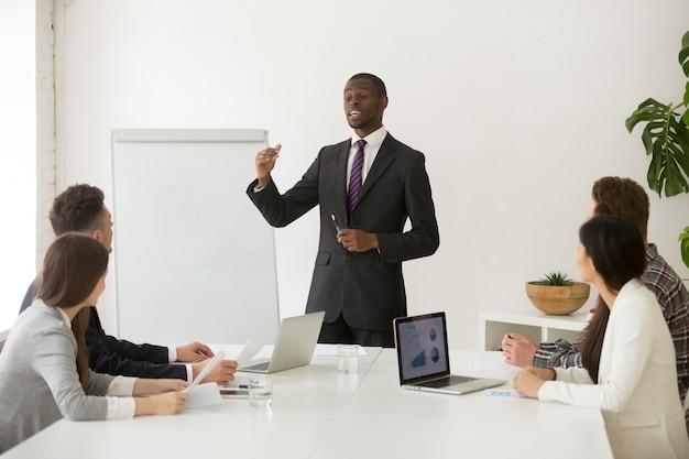 Alto-falante africano confiante ou treinador de negócios, dando a apresentação para a equipe Foto gratuita