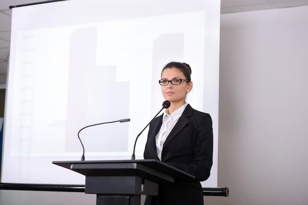 Alto-falante feminino perto de placa na conferência de negócios. Foto Premium
