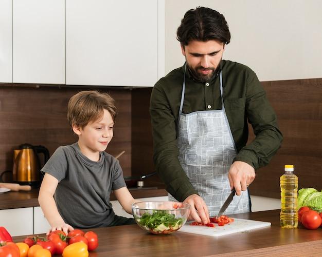 Altos ângulos filho e pai cozinhar salada Foto gratuita