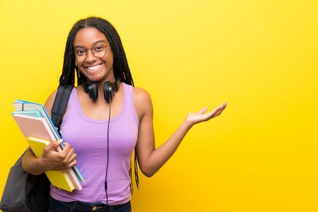 Aluna adolescente americano africano, com longos cabelos trançados sobre parede amarela segurando copyspace imaginário na palma da mão Foto Premium