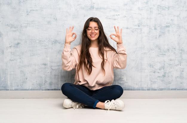Aluna adolescente estudando em uma mesa em pose de zen Foto Premium
