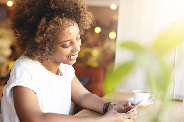 Aluna africana elegante com cabelo cacheado estiloso usando conexão de alta velocidade com a internet, checando o feed de notícias, curtindo postagens com um sorriso feliz, tomando um cappuccino, relaxando no café depois da faculdade Foto gratuita