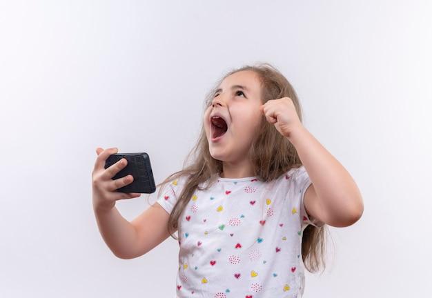 Aluna alegre vestindo camiseta branca segurando o telefone na parede branca isolada Foto gratuita
