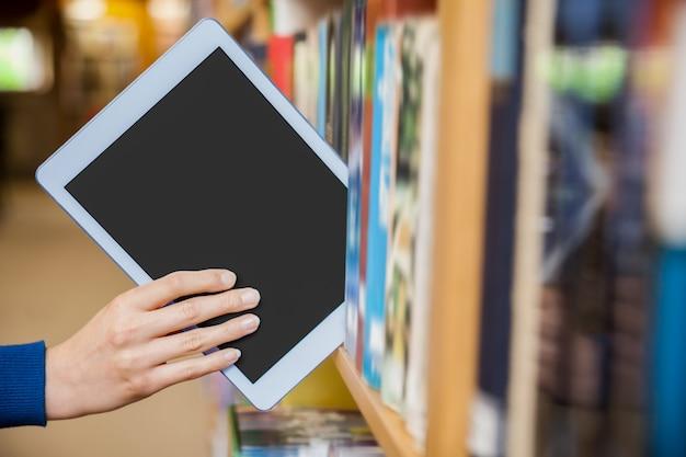 Aluna, arrumar, um, tabuleta, em, um, estante, em, a, biblioteca, em, a, universidade Foto Premium