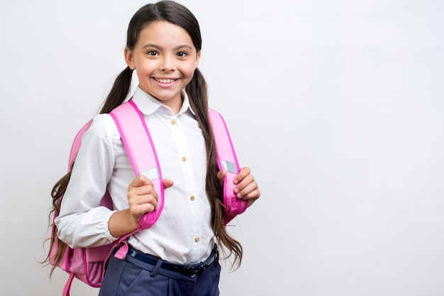Aluna hispânica entusiasta de pé com mochila Foto gratuita