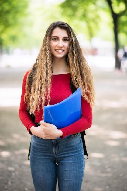 Aluna jovem adolescente andando no parque da escola Foto Premium