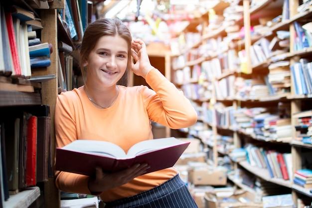 Aluna lê um livro na biblioteca antiga, uma mulher está procurando informações nos arquivos Foto Premium