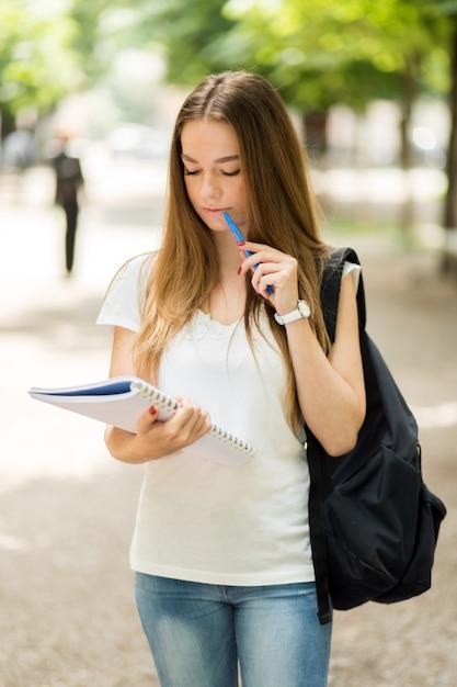 Aluna lendo um livro ao ar livre Foto Premium
