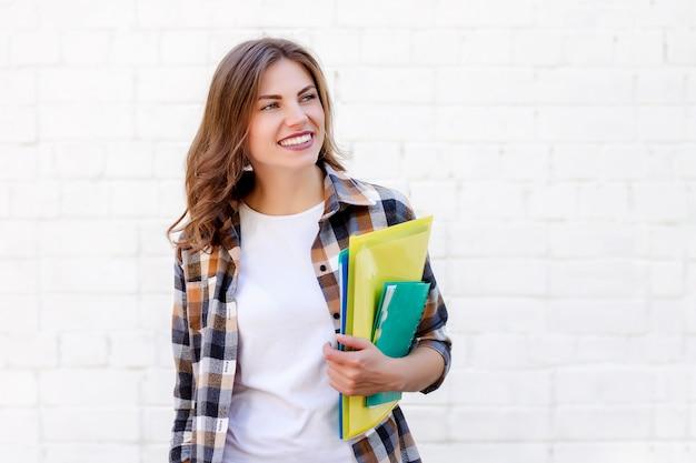 Aluna mantém pastas e um caderno nas mãos e sorri Foto Premium