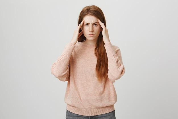 Aluna ruiva com dor de cabeça e enxaqueca Foto gratuita