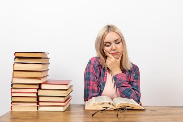 Aluna sentada com livros, lendo e pensando em branco Foto gratuita