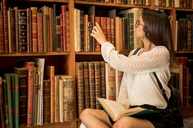 Aluna, sentando, cross-legged, com, livro aberto, em, biblioteca Foto gratuita