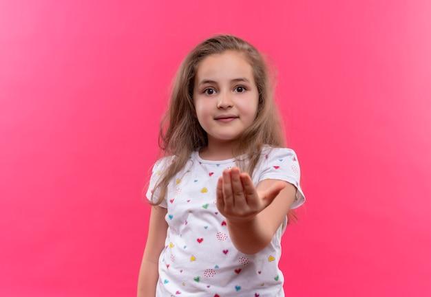 Aluna sorridente de camiseta branca estendida com a mão no fundo rosa isolado Foto gratuita