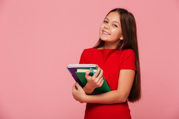 Aluna sorridente segurando livros e olhando Foto gratuita