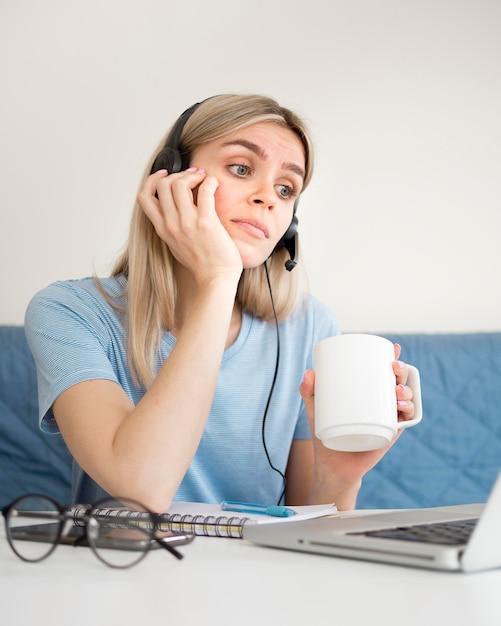 Aluna tomando café no curso on-line Foto gratuita