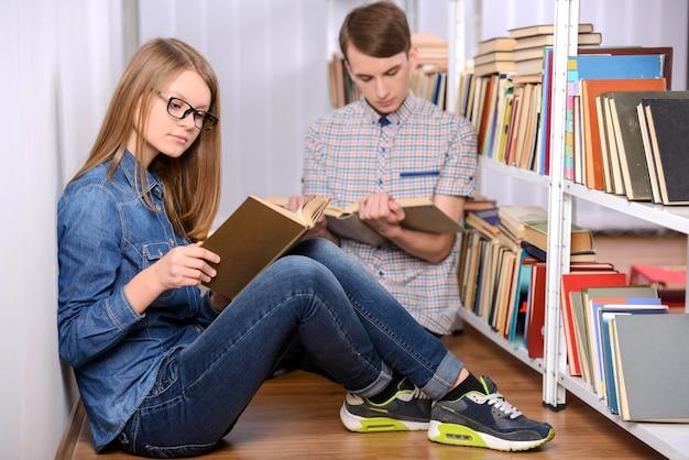 Aluno a ler um livro e usando um laptop na biblioteca Foto Premium