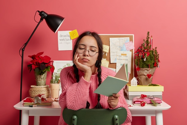 Aluno asiático sério aprende informações do livro, faz a lição de casa, usa óculos redondos e suéter, posa contra a mesa Foto gratuita