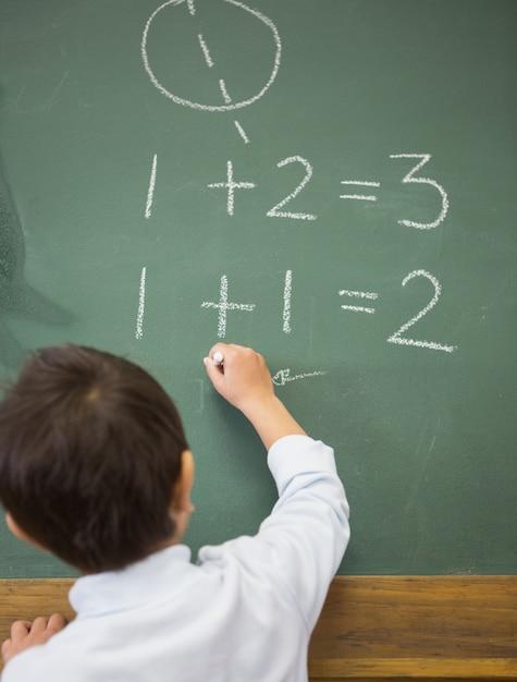 Aluno bonito que escreve matemática no quadro-negro Foto Premium