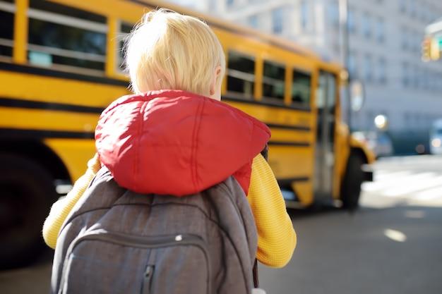 Aluno com mochila com ônibus escolar amarelo Foto Premium