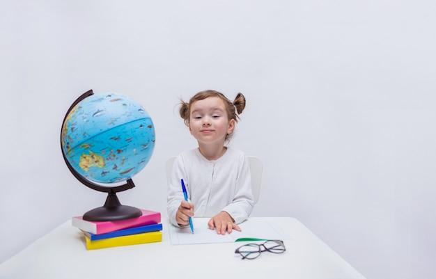 Aluno curiosa se senta em uma mesa com um caderno e caneta e olha para a câmera em um branco isolado Foto Premium