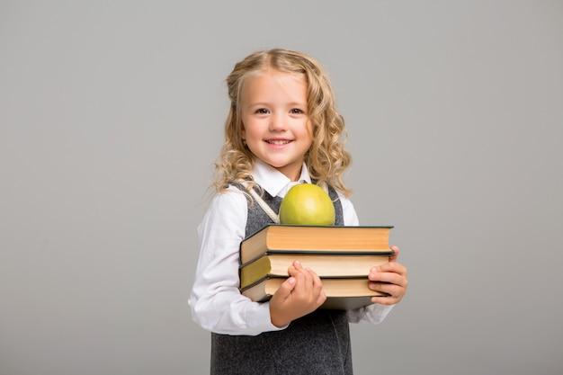 Aluno da primeira série com livros e uma maçã sorrindo sobre um fundo brilhante Foto Premium