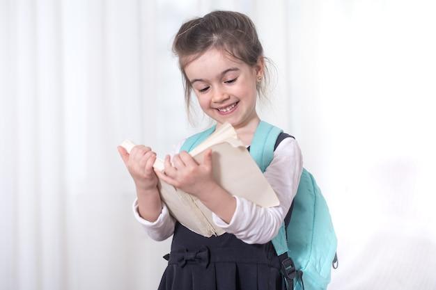 Aluno do ensino fundamental com uma mochila nos ombros, lendo um livro sobre um fundo claro. o conceito de educação e escola primária Foto gratuita