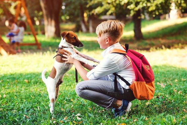 Aluno e seu cachorro andando no parque. amizade, animais e estilo de vida. jovem rapaz com jack russel terrier ao ar livre. cara feliz brincando com o cachorro na grama verde. Foto Premium