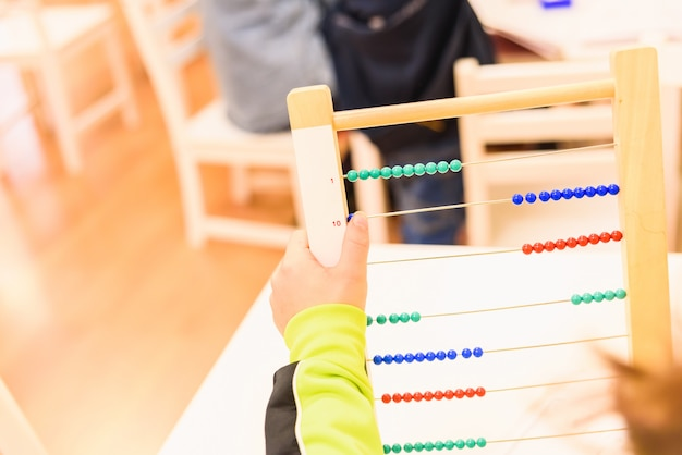 Aluno elementar usando um ábaco para aprender a fazer operações matemáticas Foto Premium
