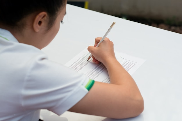 Aluno preenchendo as respostas para um teste com um lápis. Foto Premium