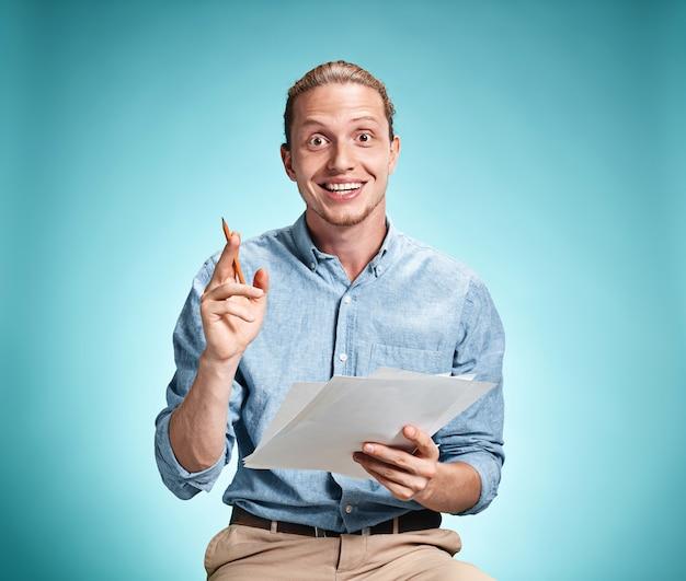 Aluno sorridente inteligente com ótima idéia segurando folhas de papel Foto gratuita