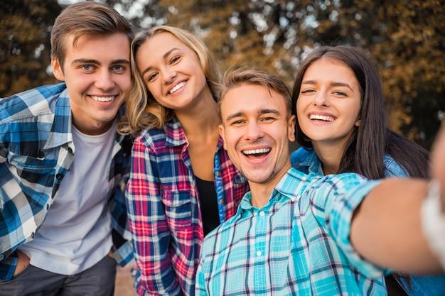 Alunos alegres tomando selfie no parque juntos. Foto Premium